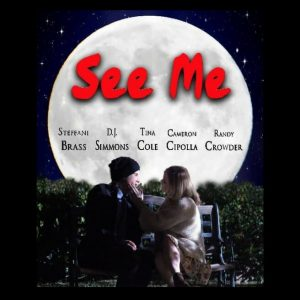 A male and Female sit on a bench. Full moon. Green bushes. Movie cover for See Me.