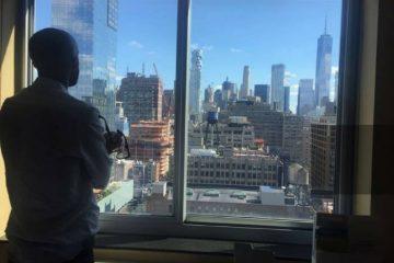 Zandir Santos: Filmmaker And Founder Of MarilynFilms.com. Man by window. NYC skyscrapers.